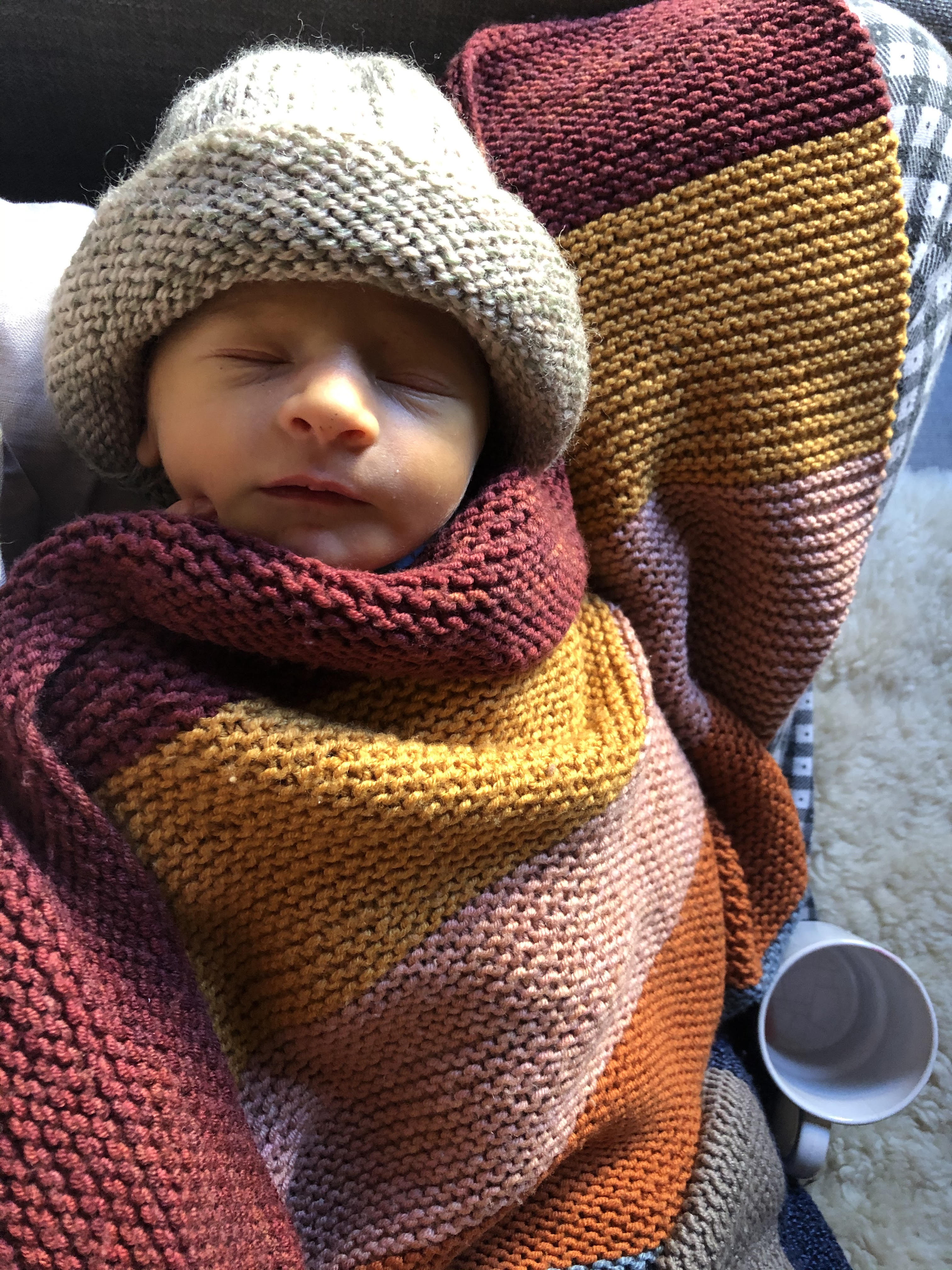 Stanley, a few days old, cosy in woollens